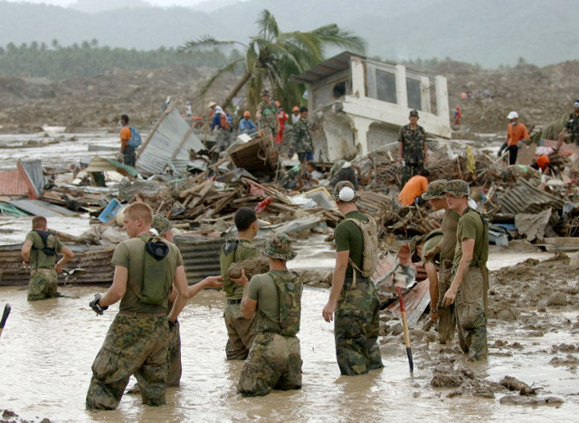 GUINSAUGON. US Marines struggle through mud to look for survivors buried under the Guinsaugon mudslide. File photo by Jay Directo/AFP