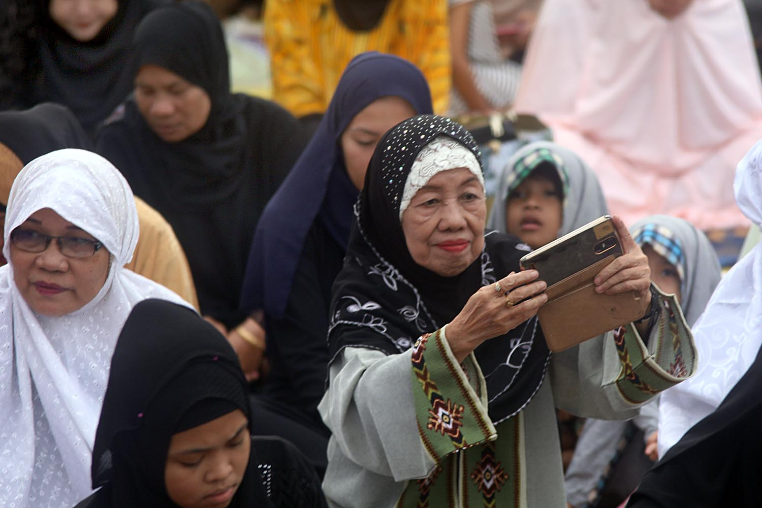 CAPTURING THE MOMENT? A woman uses her cellphone during the Eid'l Adha celebration on August 21, 2018. Photo by Darren Langit/Rappler