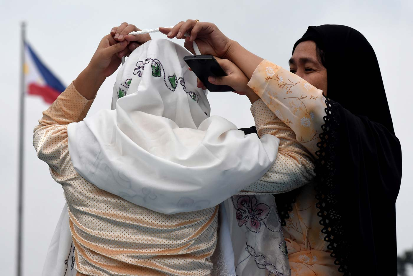 FIXING VEILS. A woman helps another fix her veil during the celebration of Eid'l Adha at the Quezon Memorial Circle on August 21, 2018. Photo by Angie de Silva/Rappler