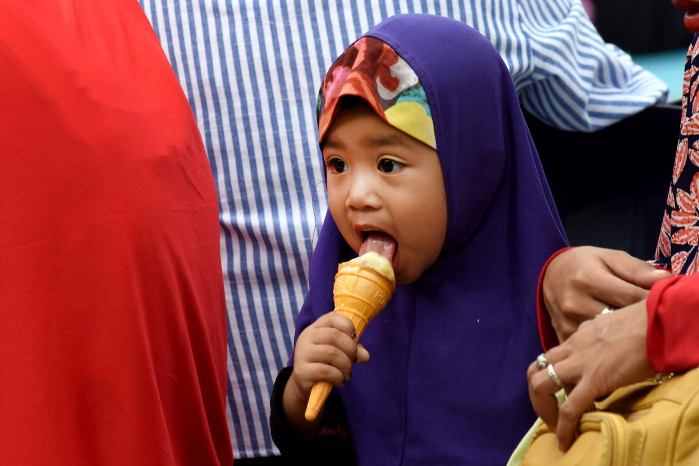 FEAST. A child licks her ice cream during the celebration of Eid'l Adha at the Quezon Memorial Circle on August 21, 2018. Photo by Angie de Silva/Rappler