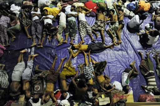 DESPERATION. A group of rescued mostly Rohingya migrants from Myanmar and Bangladesh, sleep at a government sports auditorium in Aceh province. AFP PHOTO