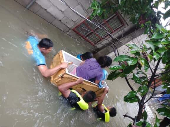 IMPROVISED BOAT. Police use a junk fridge to move a woman and her infant in Laoag City, Ilocos Norte, on August 24, 2019. Photo by Edison Deus