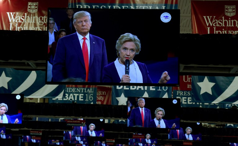 ALL EYES. TV monitors in the press room show Republican nominee Donald Trump and Democrat nominee Hillary Clinton on stage as they participate in the 2nd debate at Washington University in St. Louis, Missouri October 9, 2016. Timothy Clary/AFP