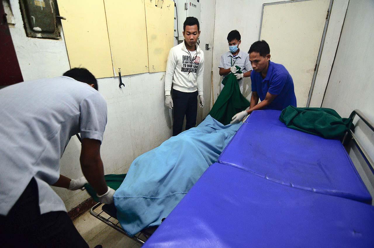 MORGUE. Hospital workers handle the corpse of Fr Marcelito Paez in the Gonzales General Hospital morgue in San Leonardo, Nueva Ecija, on December 5, 2017. Photo by Maria Tan/Rappler