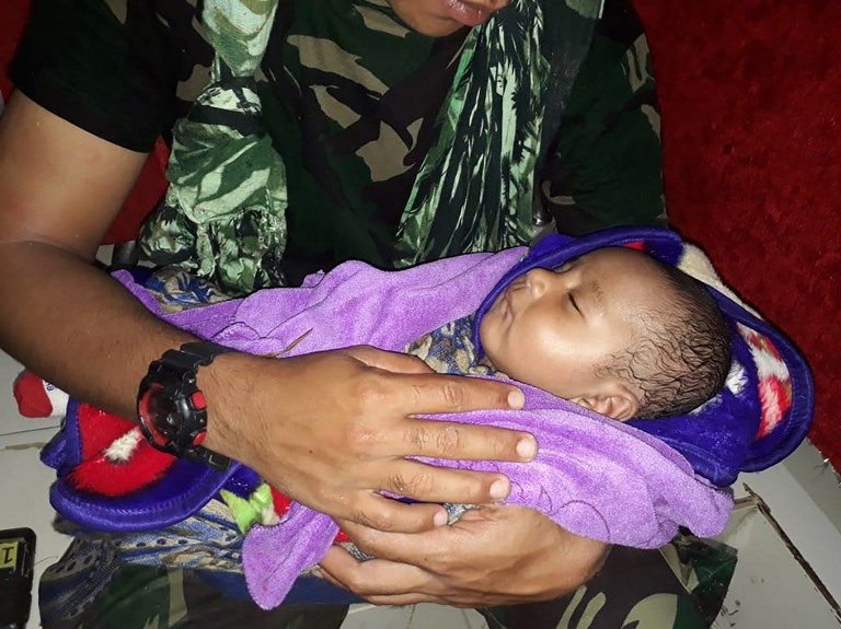 RESCUED BABY. This handout picture taken and released by the Indonesian Military on March 17, 2019 shows a soldier cradling a rescued five-month-old baby, who was trapped for hours under rubble, following flash floods in Sentani. Handout photo by Indonesian Military/AFP