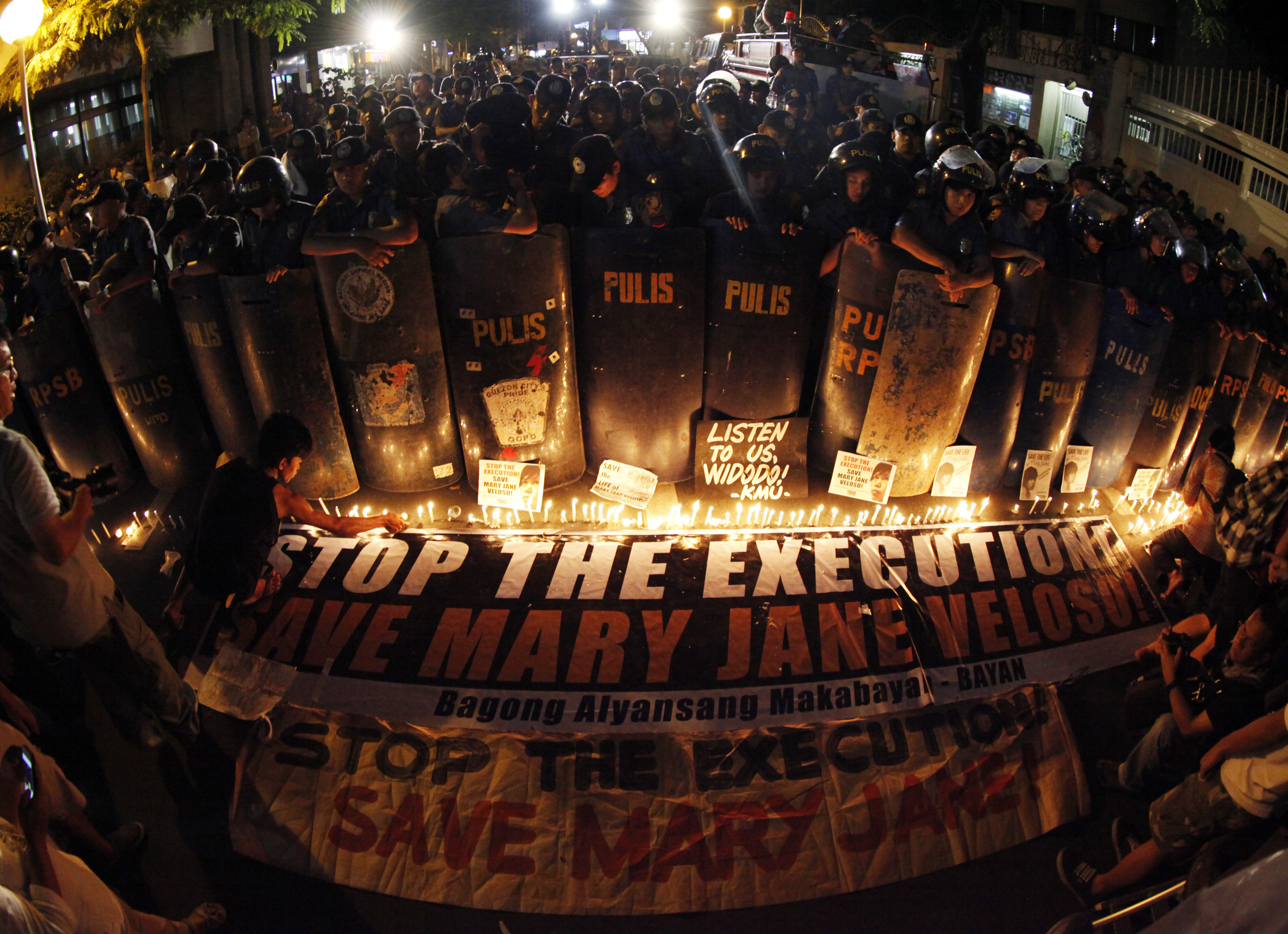 VIGIL. Filipino anti-riot police stand guard next to supporters of Mary Jane Veloso in the Philippines on April 28. Photo by Francis Malasig/EPA