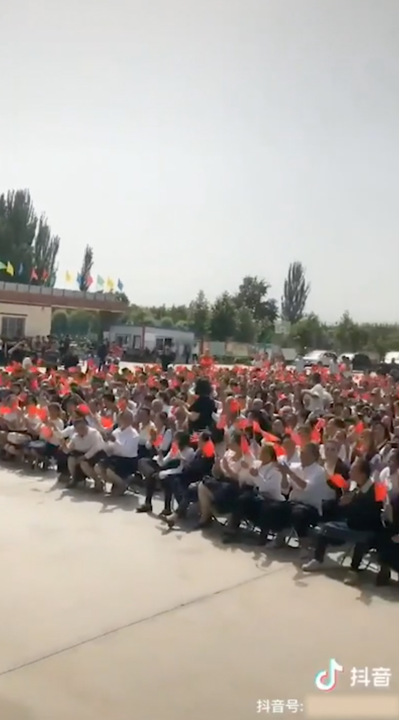 CONCERT. Crowds wave Chinese flags at what appears to be a propaganda concert in Yopurga County, near Kashgar, Xinjiang