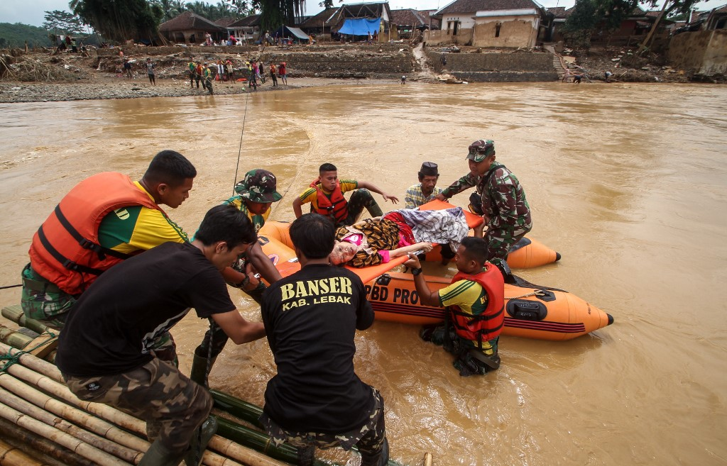 HELP. Rescuers help a sick woman cross the river to get medical assistance at the Sukarame village in Lebak, Banten province on January 3, 2020, after flooding triggered by heavy rain which started on New Year's Eve hit the area. Photo by Sammy/AFP