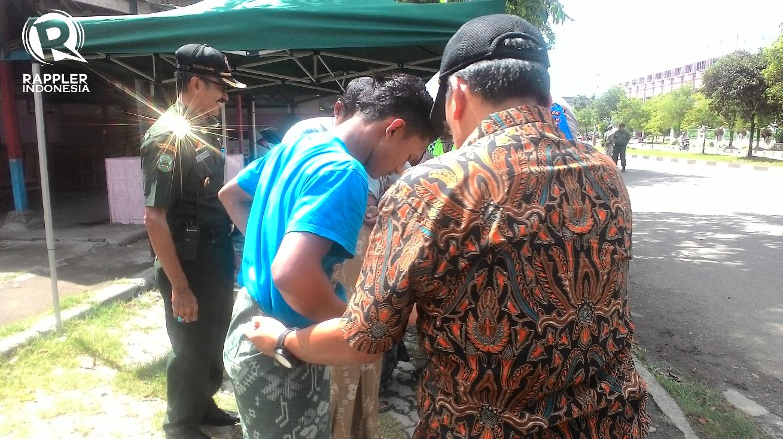 SARUNG. Para pelanggar razia busana laki-laki diberikan sarung oleh petugas pada Kamis, 12 Oktober. Foto oleh Habil Razali/Rappler