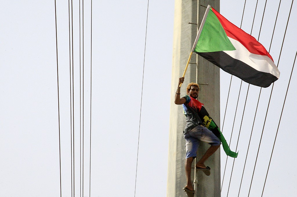 SUDAN. In this file photo, a Sudanese demonstrator waves his national flag in front of the Algerian embassy as people celebrate in Khartoum on August 4, 2019, after Sudan's army rulers and protest leaders signed a hard-won constitutional declaration that paves the way for a transition from August 18 to civilian rule following more than seven months of often deadly street rallies. File photo by Ebrahim Hamid/AFP