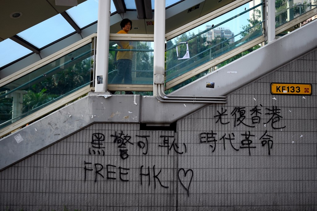 FREE HK. This picture taken on August 9, 2019 shows a woman walking on a pedestrian bridge adorned with u0022Free HKu0022 graffiti in the Wong Tai Sin district of Hong Kong. Photo by Manan Vatsyayana/AFP
