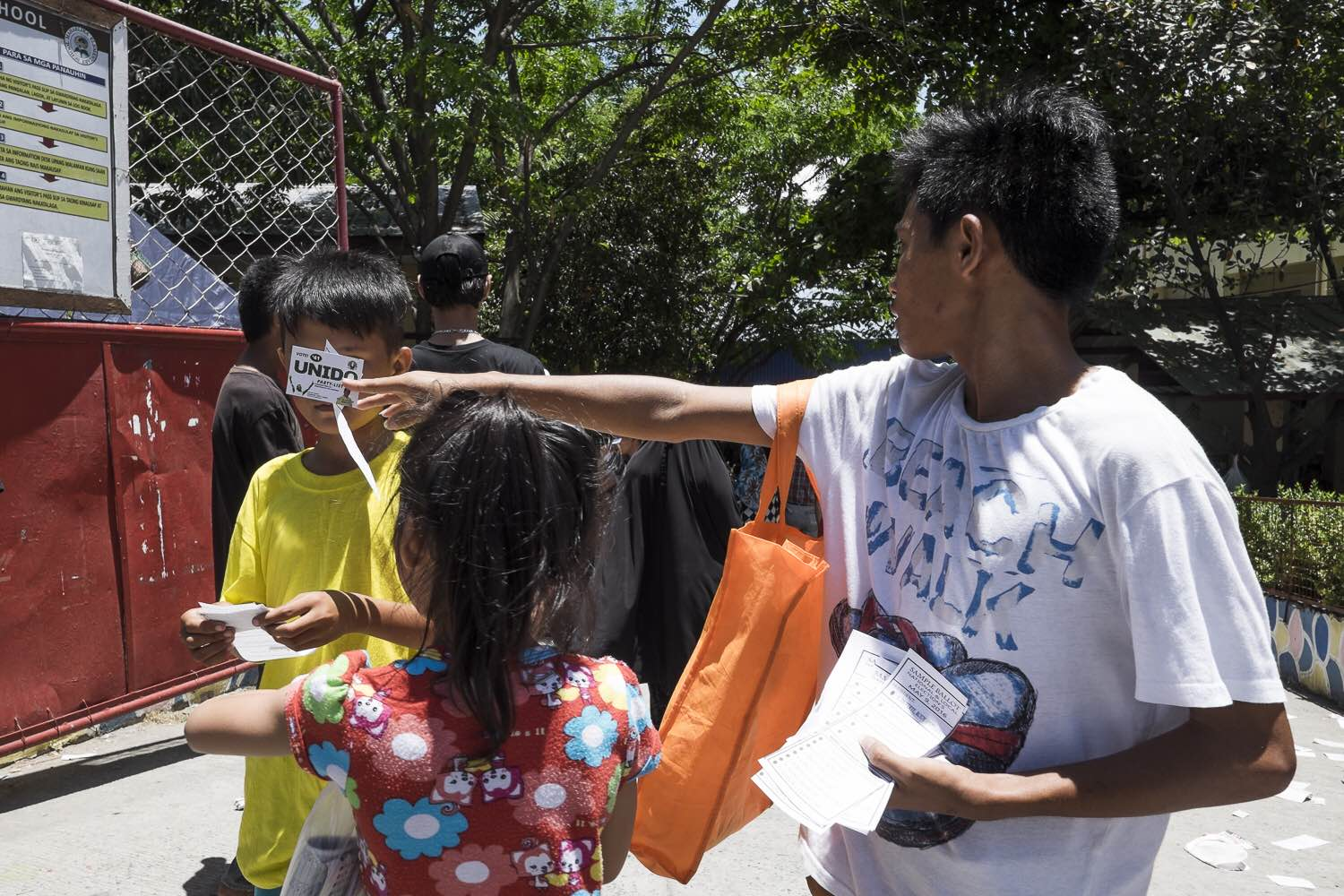CHILDREN. Underage children are seen distributing campaign materials and sample ballots near a precinct in Taguig. Photo by Pat Nabong/Rappler