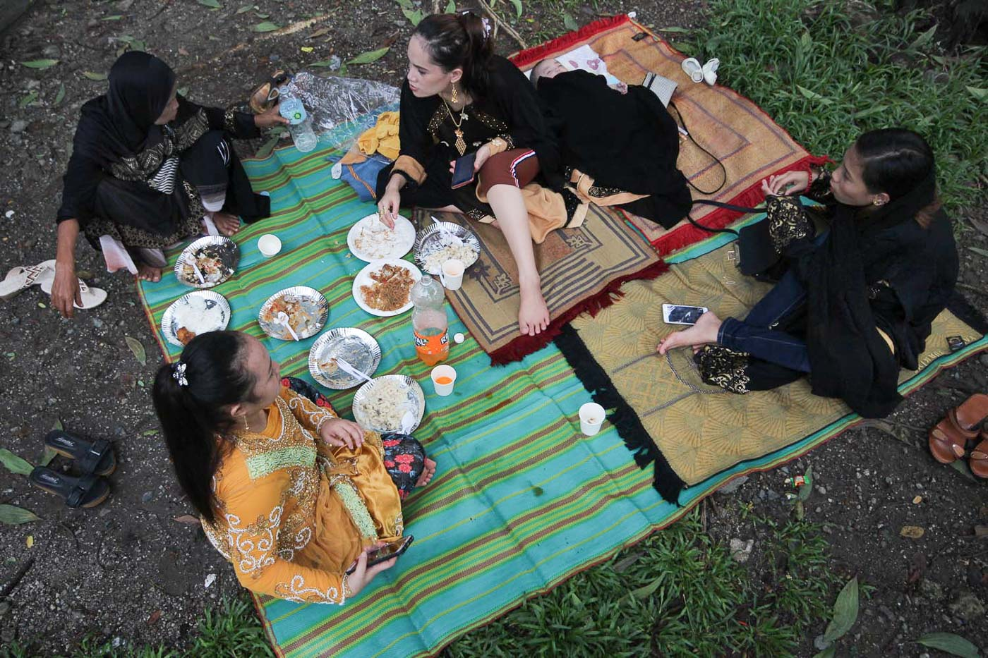 FEAST. A family shares their first meal after the prayers in celebration of Eid al-Fitr at the Quezon City Memorial Circle. Photos by Darren Langit/Rappler