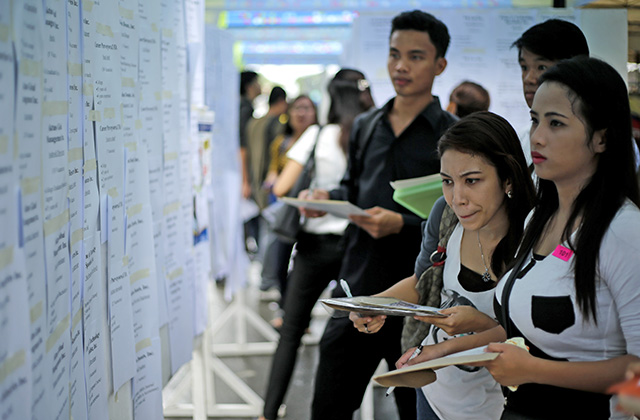 JOB HUNT. Prospective employees check potential employers at a jobs fair. File photo by Ritchie Tongo/EPA
