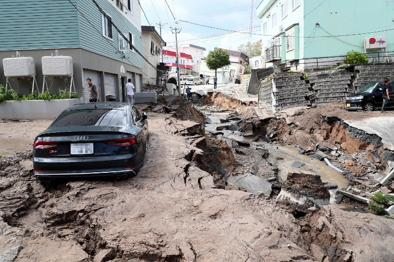 DAMAGED ROADS. A car is seen stuck on a road damaged by an earthquake in Sapporo, Hokkaido prefecture on September 6, 2018. Photo by Jiji Press/AFP