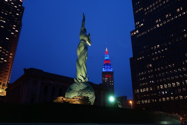 RNC HOST CITY. An illuminated statue on Cleveland's 'Mall' is shown with the Terminal Tower in the background, itself illuminated in the colors of the Cleveland Cavaliers basketball team in Cleveland, Ohio on April 6, 2016. Cleveland will host the Republican National Convention from July 18-21, 2016. William Edwards/AFP