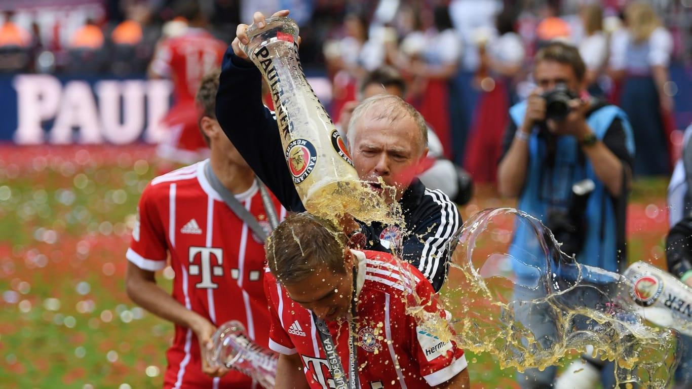 BIERDUSCHE. Asisten pelatih Hermann Gerland menyirami Philipp Lahm dengan weissbier. Foto dari fcbayern.com