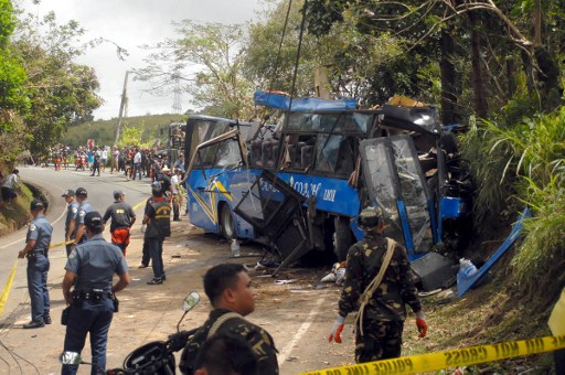 Police and soldiers stand guard next to a tourist bus which hit an electric post in Tanay town, Rizal province, east of Manila on February 20, 2017. Stringer/AFP