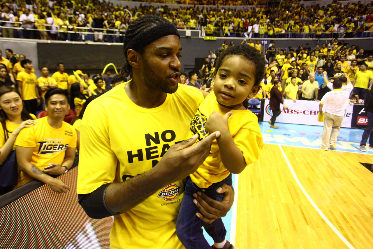 DADDY KARIM. Karim Abdul holds his child after UST's Game 2 victory. Photo by Josh Albelda/Rappler
