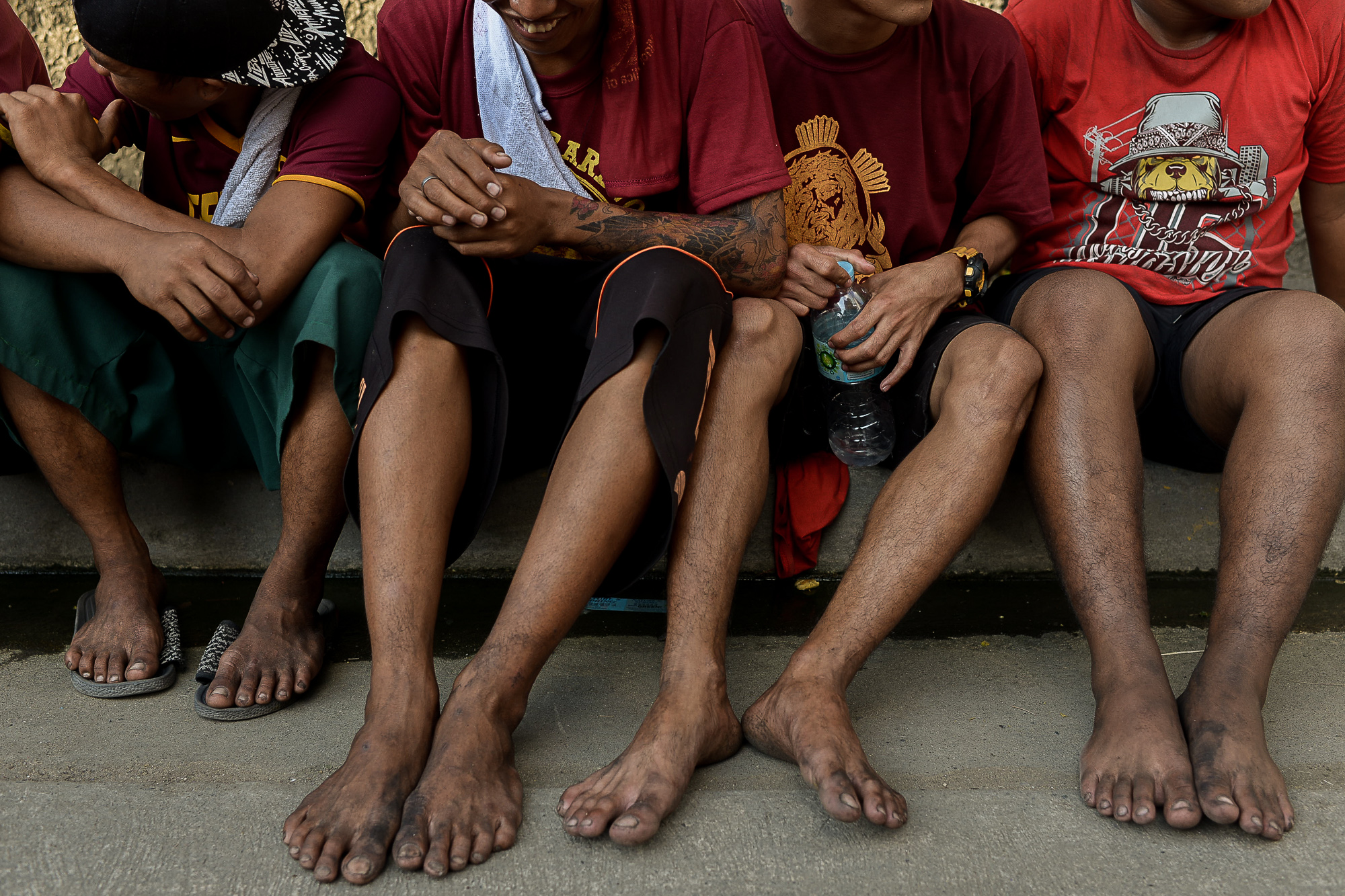 ZEAL. Young men rest on a sidewalk after walking the procession. Photo by Eloisa Lopez/Rappler