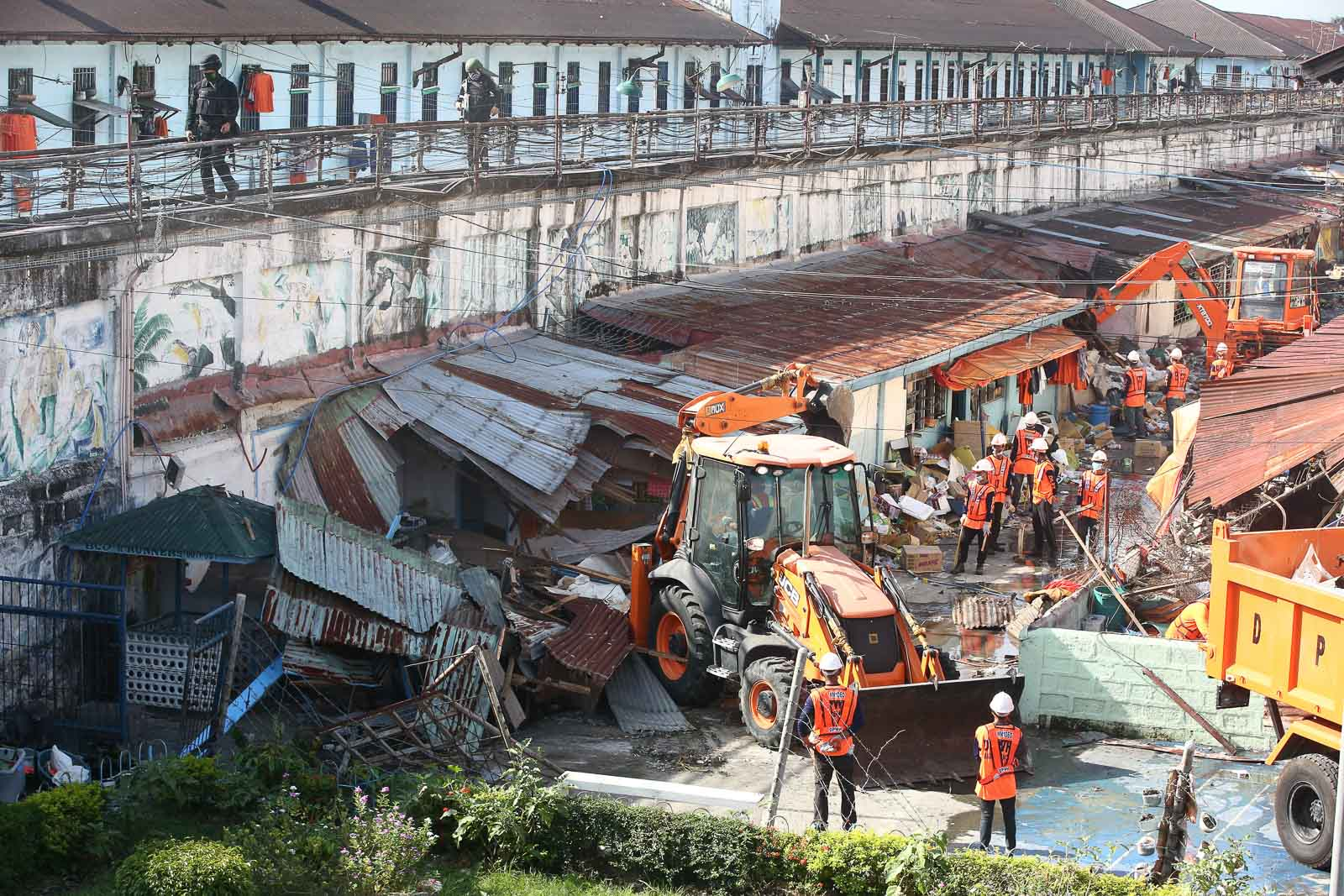 DEMOLITION. Workers use heavy equipment as they dismantle illegal structures as ordered by newly installed BuCor chief Gerald Bantag and NCRPO chief Guillermo Eleazar inside the New Bilibid Prison in Muntinlupa City on October 9, 2019. Photo by Ben Nabong/Rappler