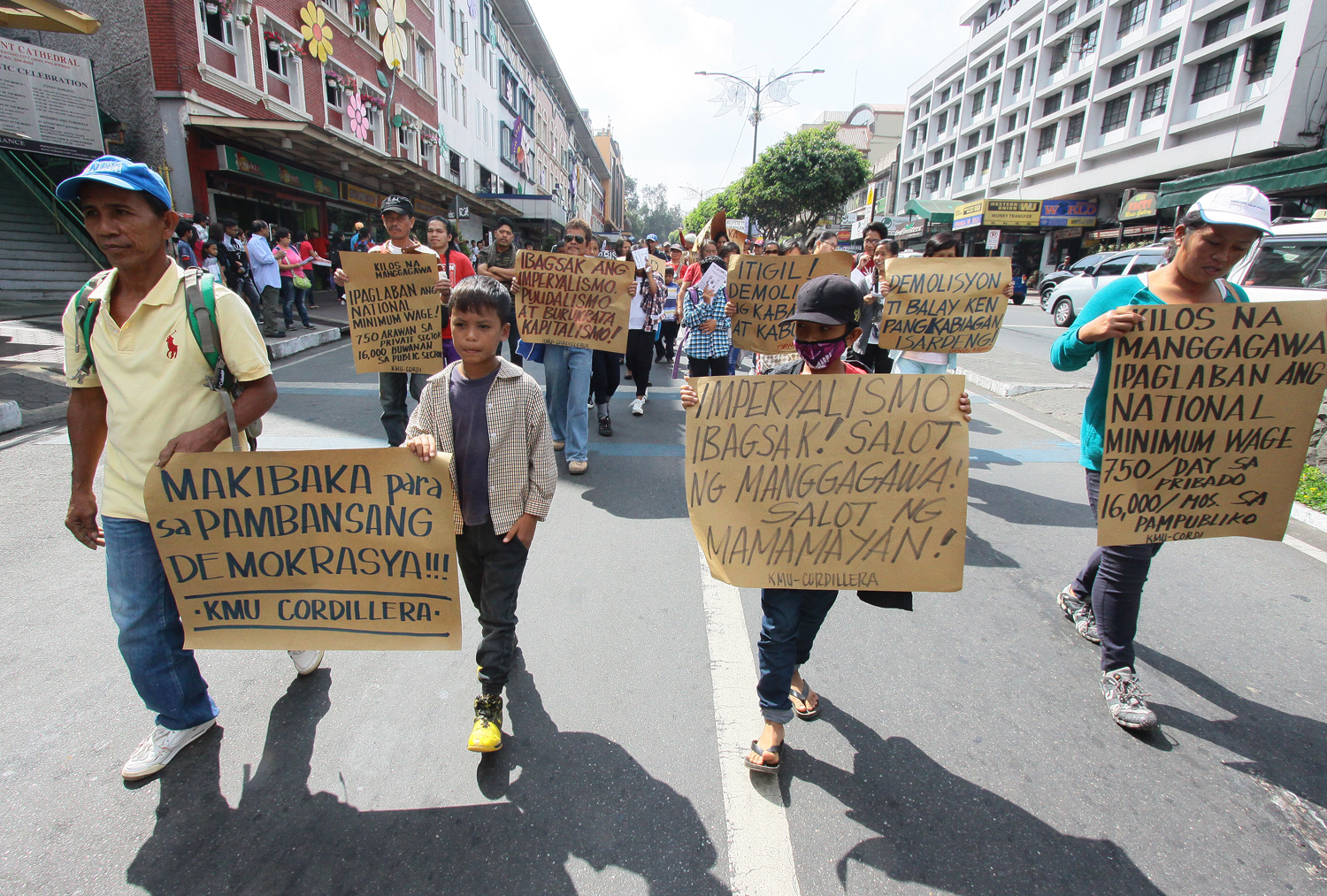 MARCHING. Militants together with their children carry placards in a march rally along the central business district of Session road Baguio City 1 May during the celebration of Labor Day. Photo by Mau Victa/Rappler