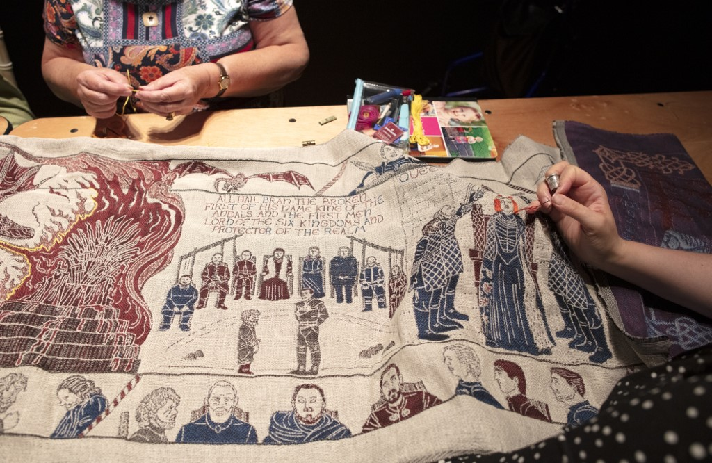 ALMOST DONE. Embroiderers work on the final section of a tapestry depicting the hit television series Game of Thrones at the Ulster Museum Photo by Paul Faith / AFP