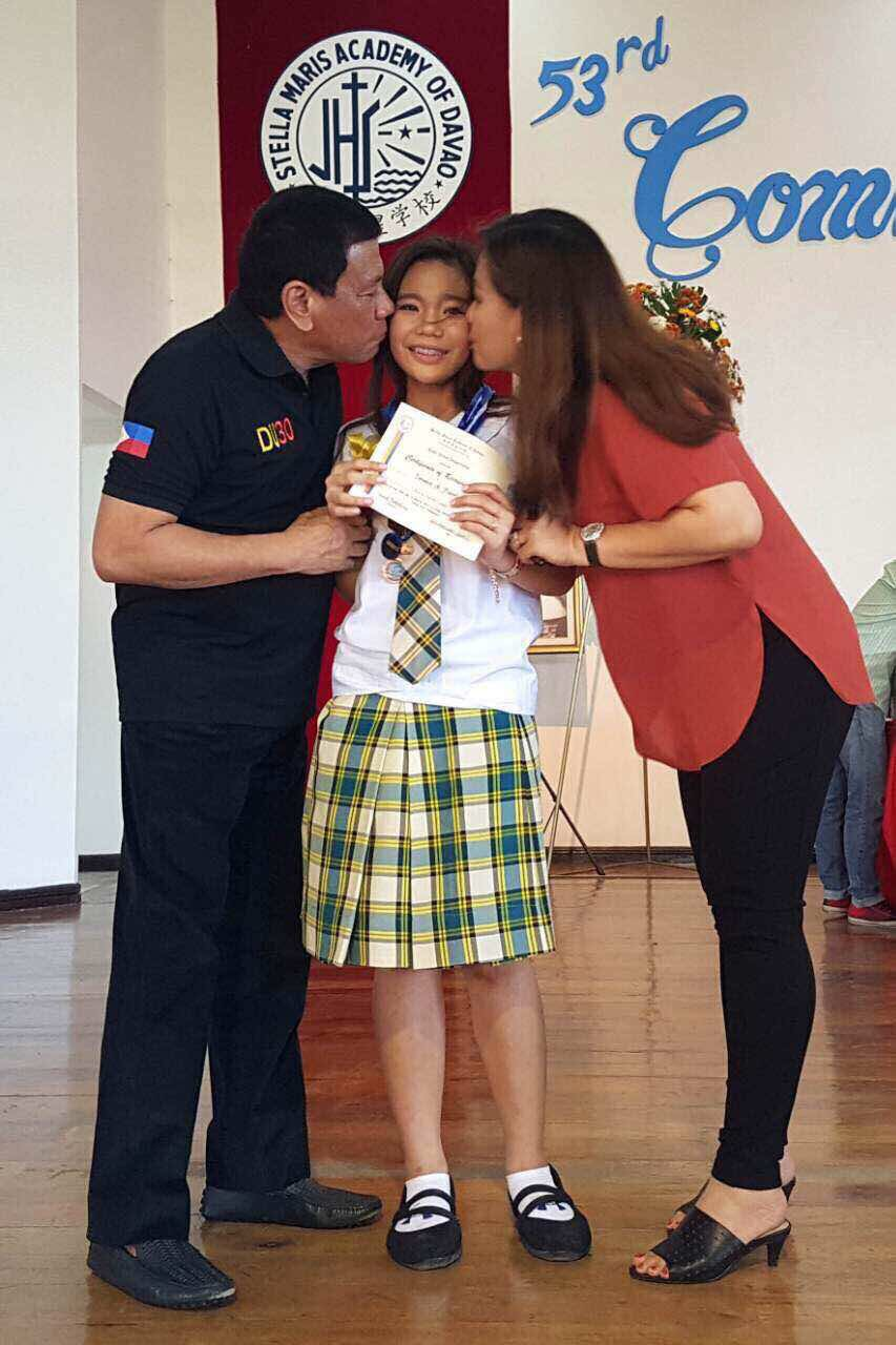 DOTING PARENTS. President Rodrigo Duterte and common-law-wide Honeylet Avancena kiss daughter Kitty on her graduation day. Photo from Special Assistant to the President Bong Go