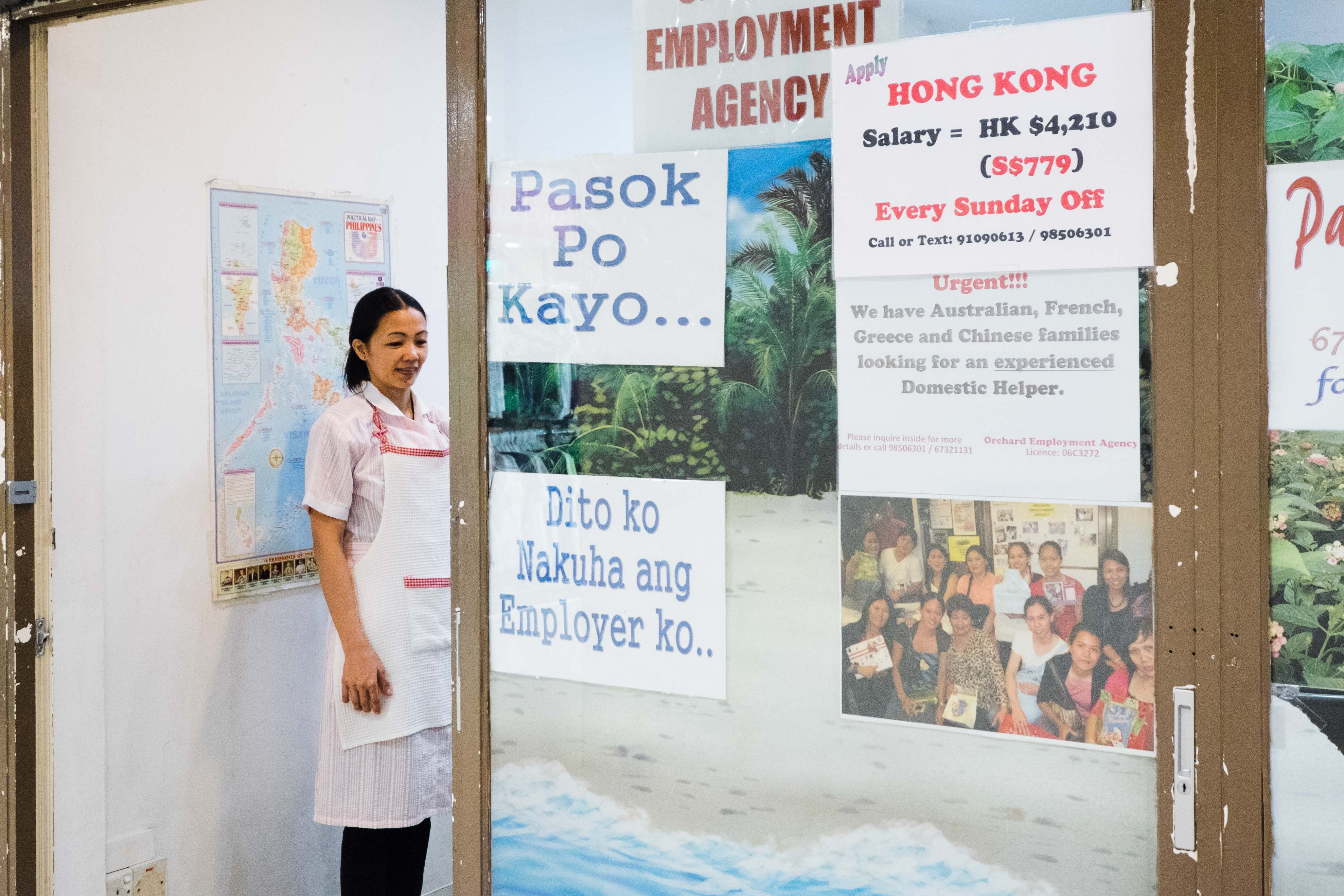 A woman poses for a picture in an employment agency in Lucky Plaza.
