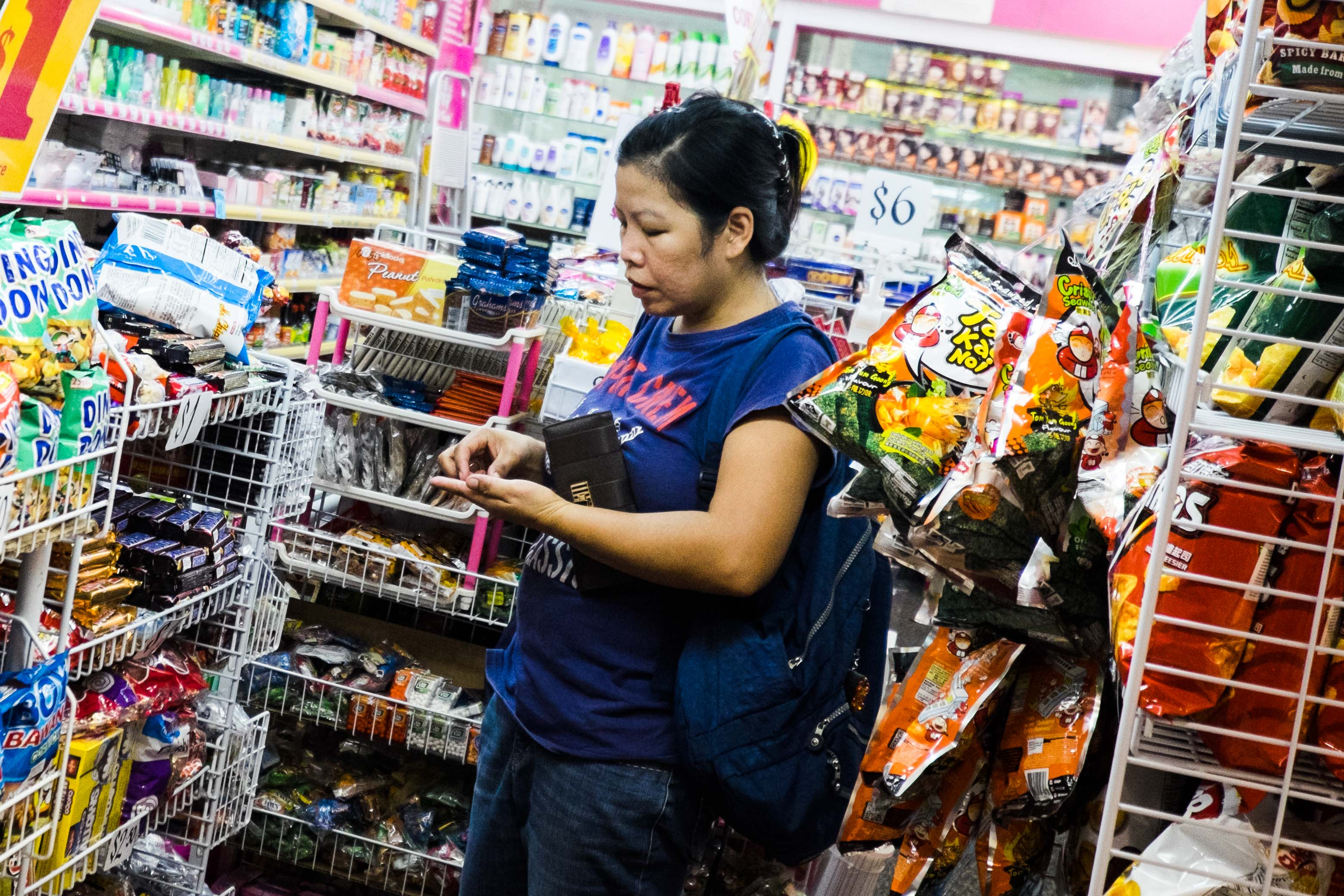 A Filipina domestic worker buys Filipino products in a stall in Lucky Plaza.