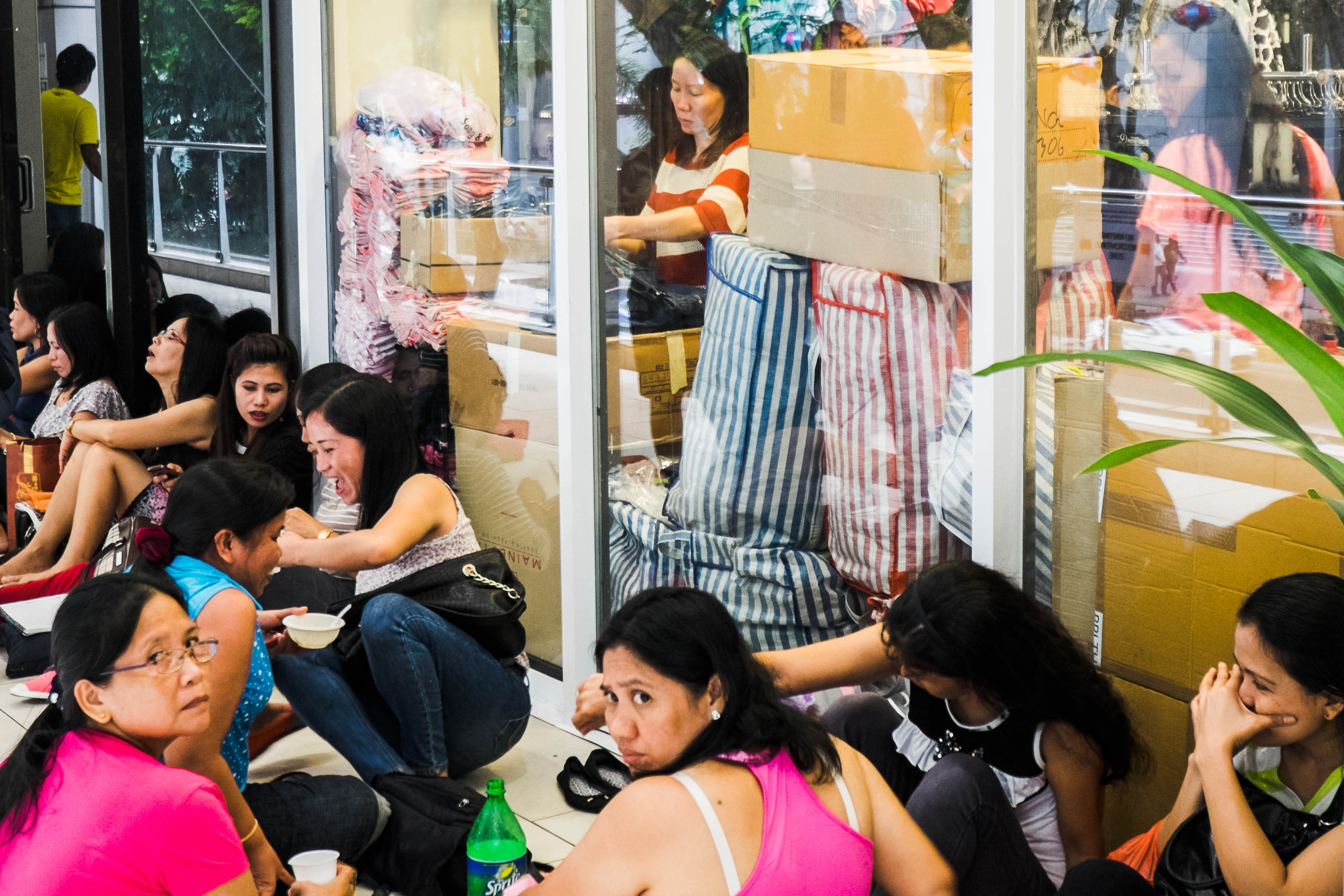 Overseas Filipino Workers sit on the floor of one of Lucky Plaza's balconies where many OFWs share meals during their day-off.