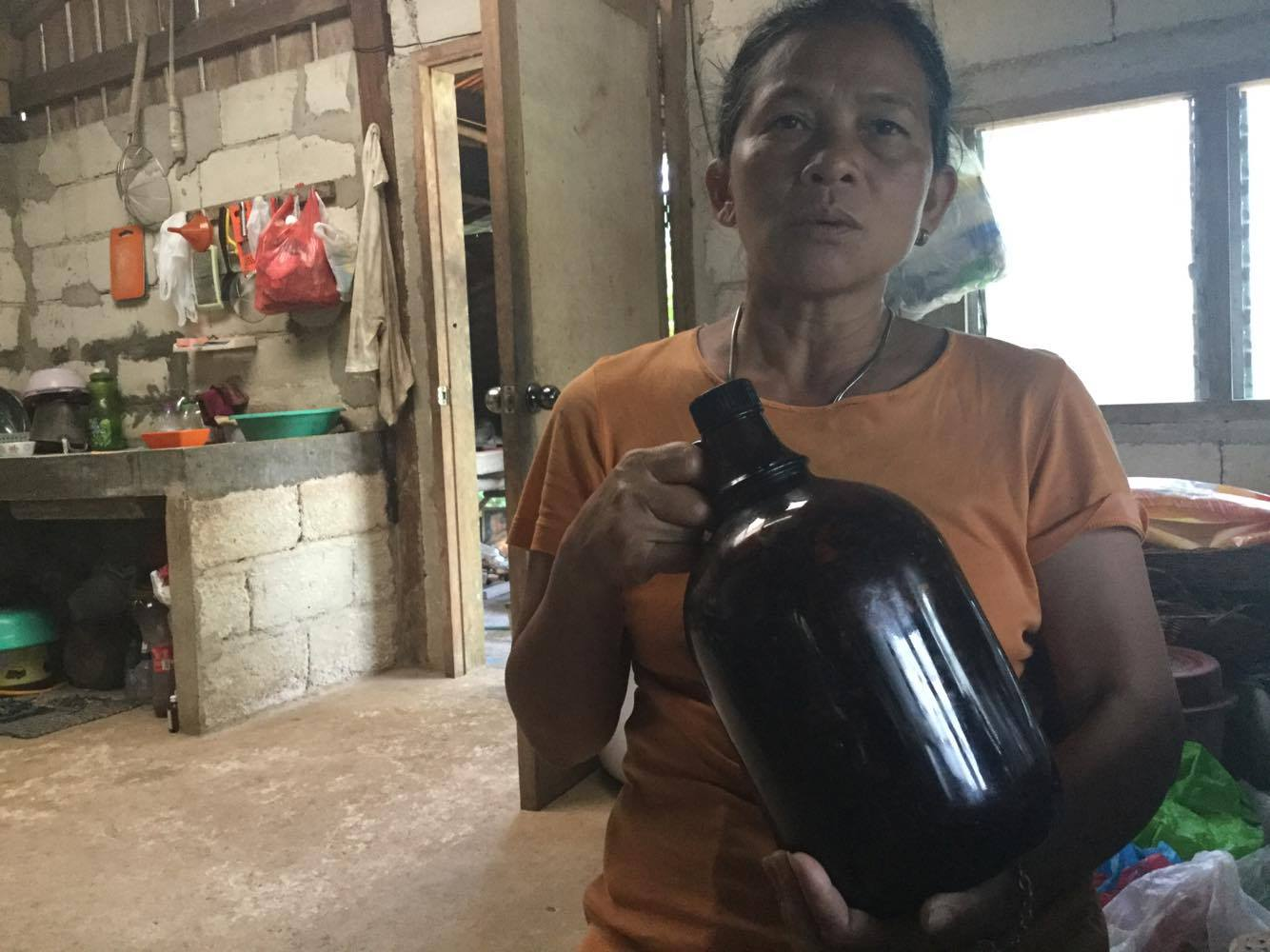 IN HER FATHER'S FOOTSTEPS. Juanita holds up the 50-year-old demijuana owned by her late father, Pedro Tumapon, one of the foremost mananambals in Siquijor
