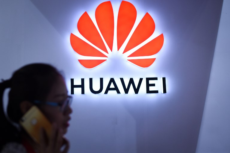 HUAWEI. In this file photo taken on July 8, 2018 a woman uses her mobile phone in front of a Huawei logo at Beijing International Consumer Electronics Expo in Beijing.Photo by Wang Zhao/AFP