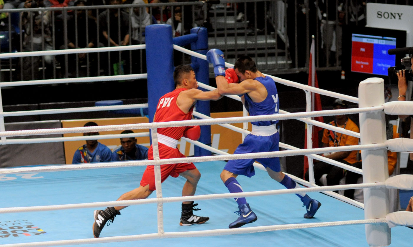 ON TO THE SEMIS. Mario Fernandez of the Philippines lands a right hand through the gloves of Vietnam's Tran Phu Cuong to advance to the semis. Photo by Adrian Portugal/Rappler