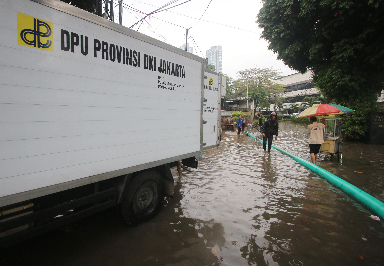 Petugas Dinas Tata Air melakukan penyedotan air dengan mesin pompa saat banjir menggenangi kawasan Kemang, Jakarta Selatan, pada 4 Oktober 2016. Foto oleh Reno Esnir/Antara