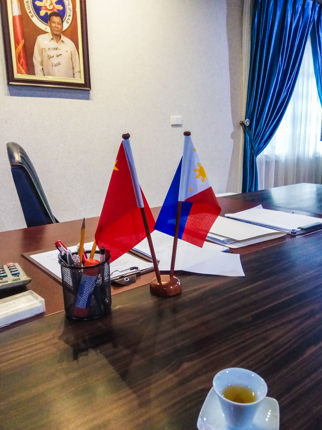 CLOSE TIES. A desk in Michael Yang's office stands in front of a signed portrait of President Rodrigo Duterte. Sourced photo