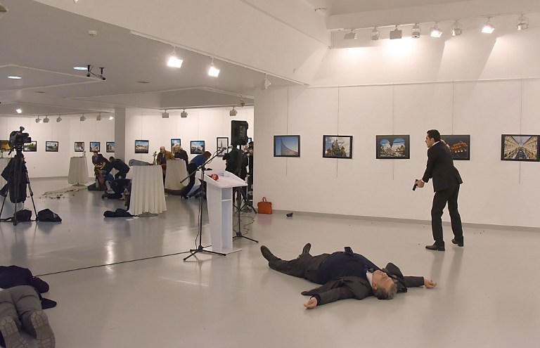 CHAOS. This picture taken on December 19, 2016 shows Andrey Karlov (2ndR), the Russian ambassador to Ankara, lying on the floor after being shot by a gunman (R) during an attack during a public event in Ankara. Stringer/AFP