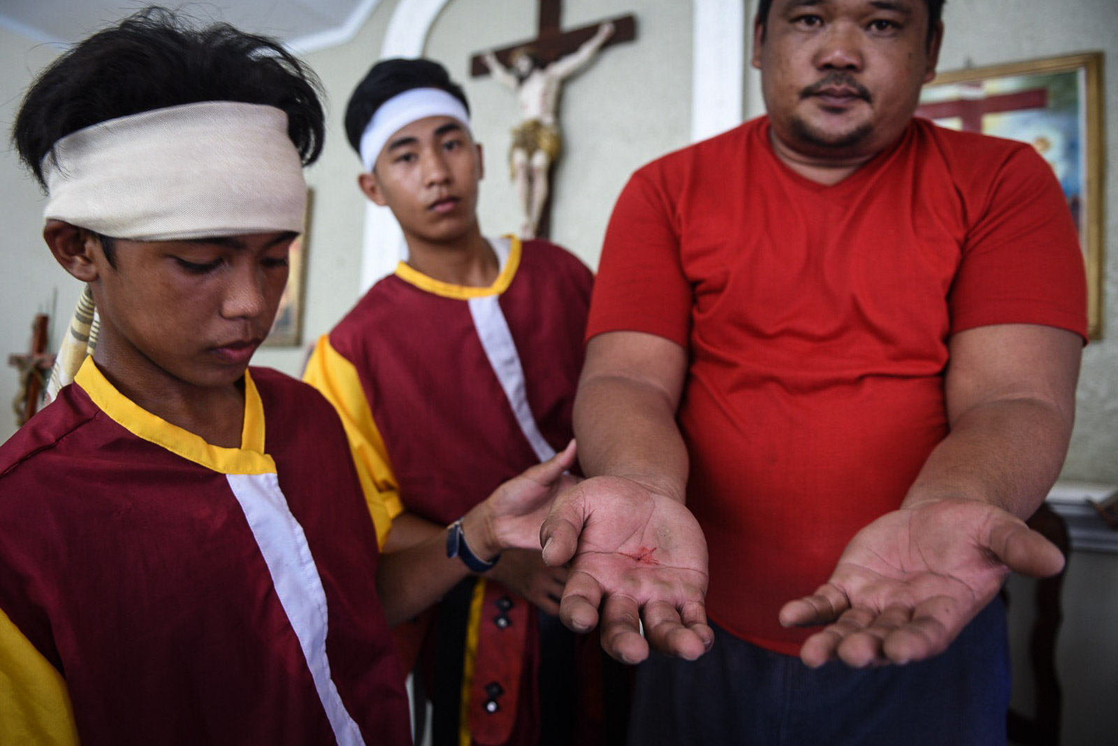 THE WOUND. Marcelino shows his hands to the crowd after the Passion play.