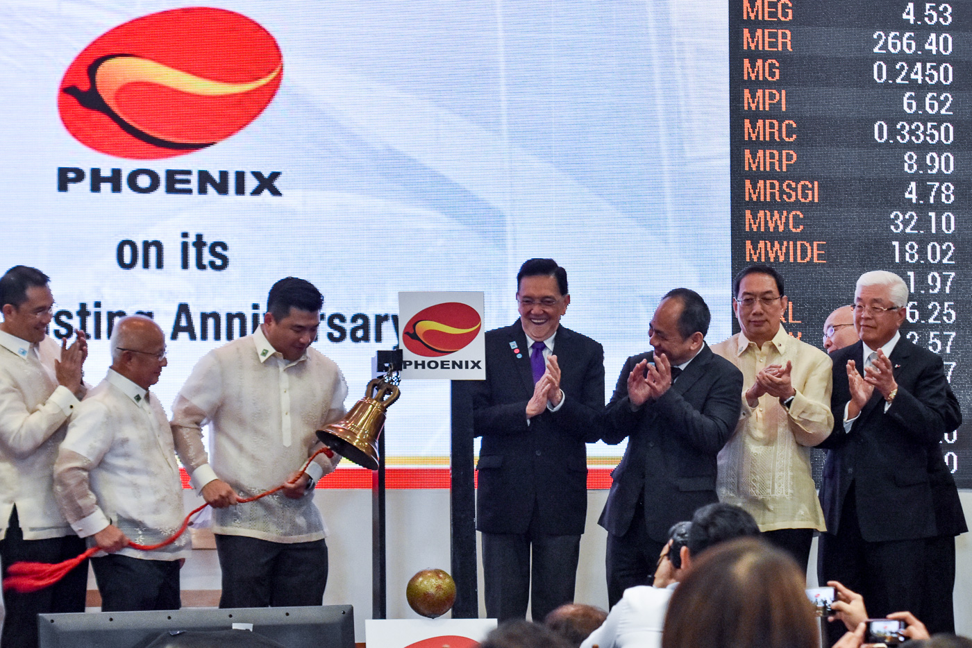 PROUD MOMENT. Phoenix Petroleum CEO Dennis Uy and chairman Domingo Uy ring the PSE bell.