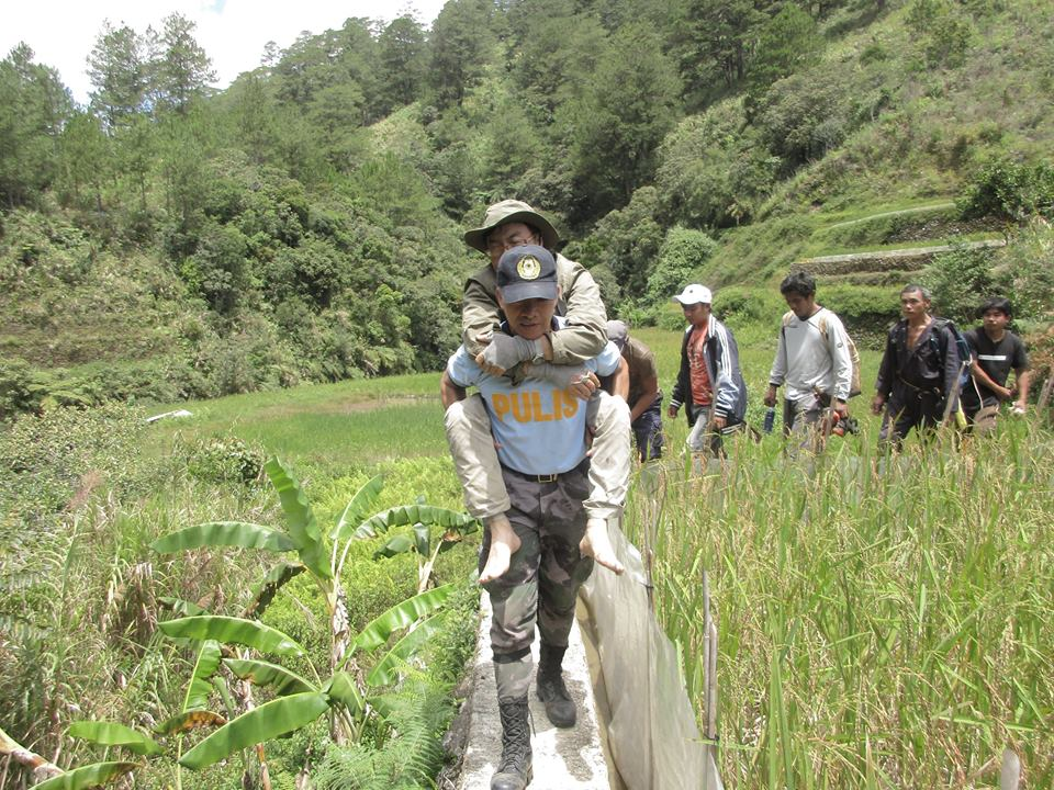 RESCUED. Barlig town police carry Choi Sungkyu across rice paddies. He has been brought to a hospital for treatment after his 11-day ordeal.