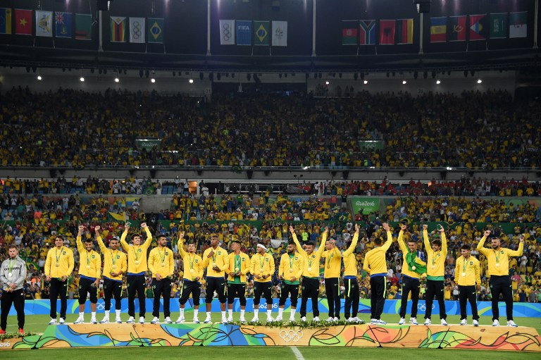 CHAMPS. Brazil's forward Neymar (C) and teammates celebrate on the podium during the medal presentation following the Rio 2016 Olympic Games men's football gold medal match between Brazil and Germany at the Maracana stadium in Rio de Janeiro on August 20, 2016. Vanderlei Almeida/AFP