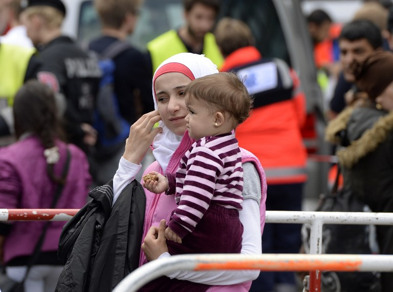 WAITING. In this file photo, a migrant woman wait with her child waits in front of the main train station in Munich, southern Germany, on September 13, 2015. Christof Stache/AFP