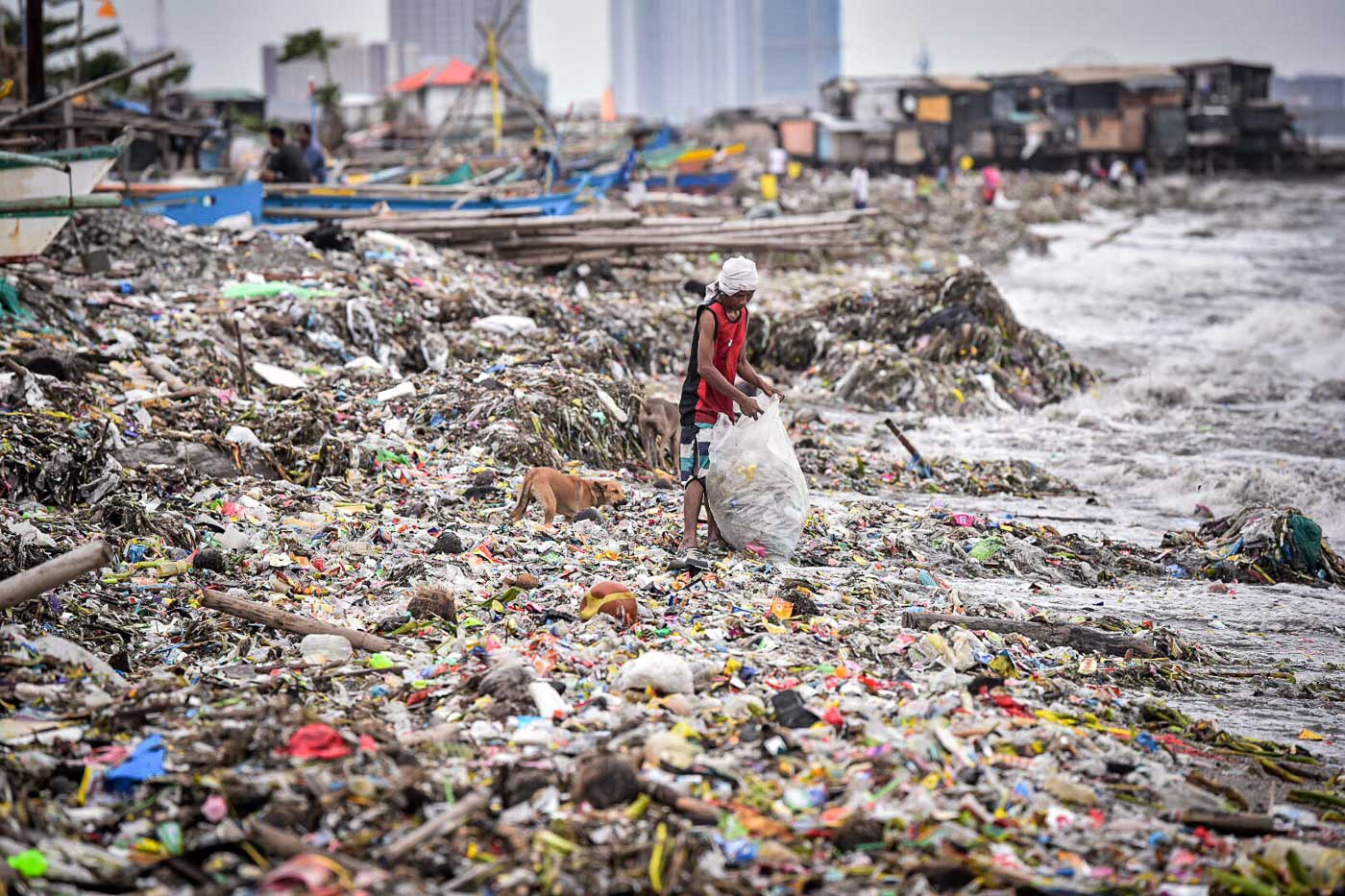ENTERPRISING. A resident of Baseco, Manila, salvages recyclables from the trash washed ashore by wave surges from Manila Bay. Photo by Alecs Ongcal/Rappler