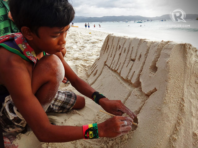 SAND ART. A local kid intently sculpting Boracayu2019s fine sand. Photo by Rhea Claire Madarang