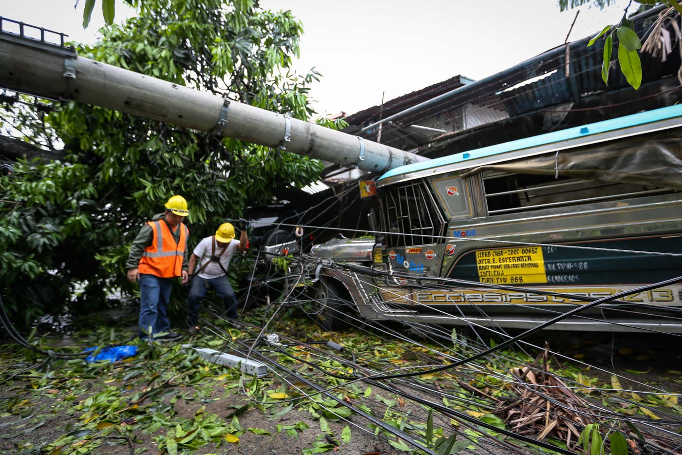 POWER OUT. An electric post hits a parked jeepney in West Riverside, San Francisco del Monte in Quezon City, after being toppled by strong winds. Photo by Maria Tan/Rappler