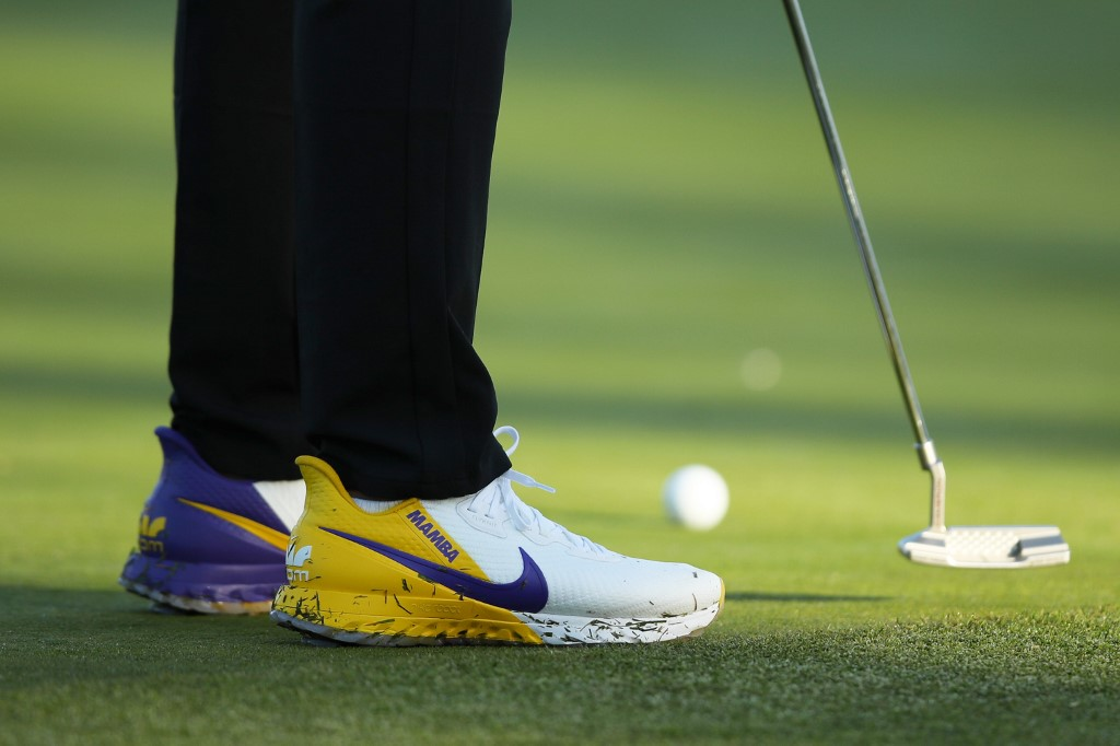 COLORWAY. Brooks Koepka lines up a putt wearing golf shoes featuring the Lakers' purple and gold. Photo by Joe Scarnici/Getty Images/AFP
