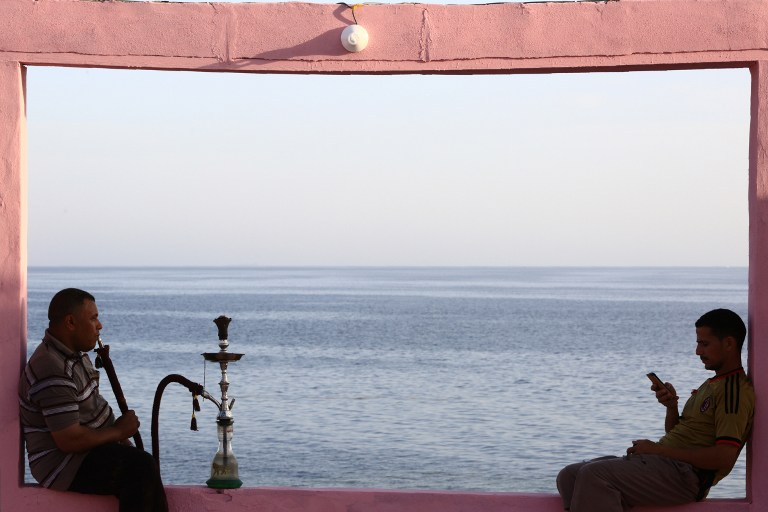 REFORMS COMING. Two men sit on wall overlooking the Red Sea at a popular cafe in the northwestern Saudi town of al-Wajh on April 25, 2016. Photo by Mohammed Al-Buhaisi/AFP