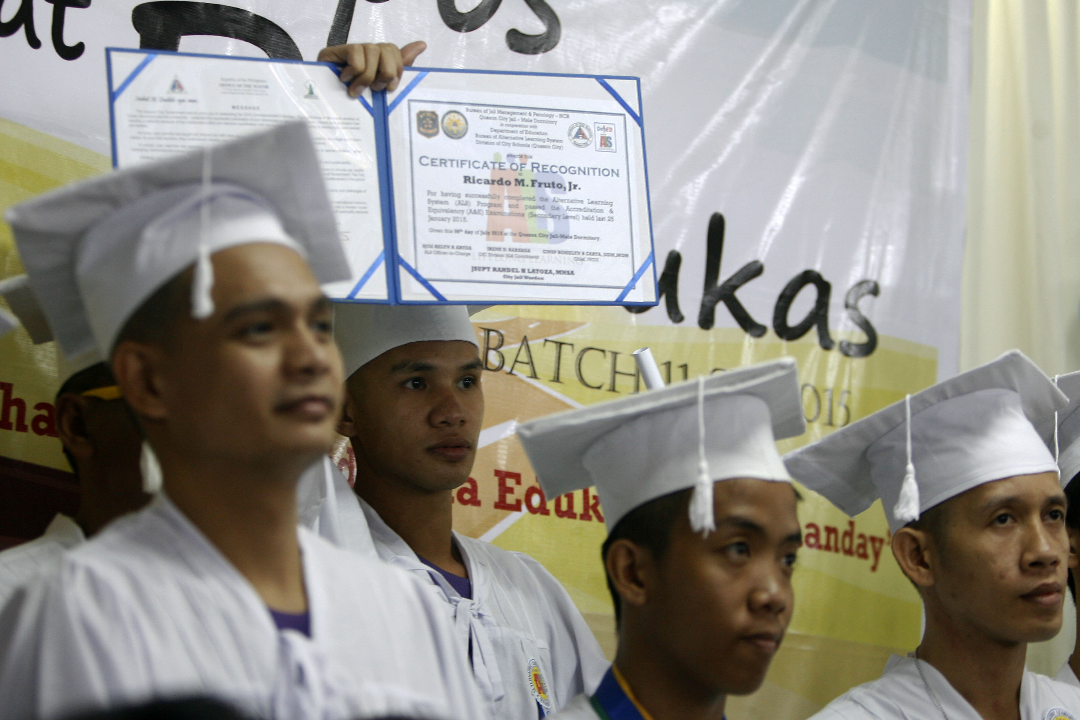 A detainee proudly shows his certificate of recognition during their graduation at the Alternative Learning System (ALS) program of the Department of Education inside the Quezon City Jail.