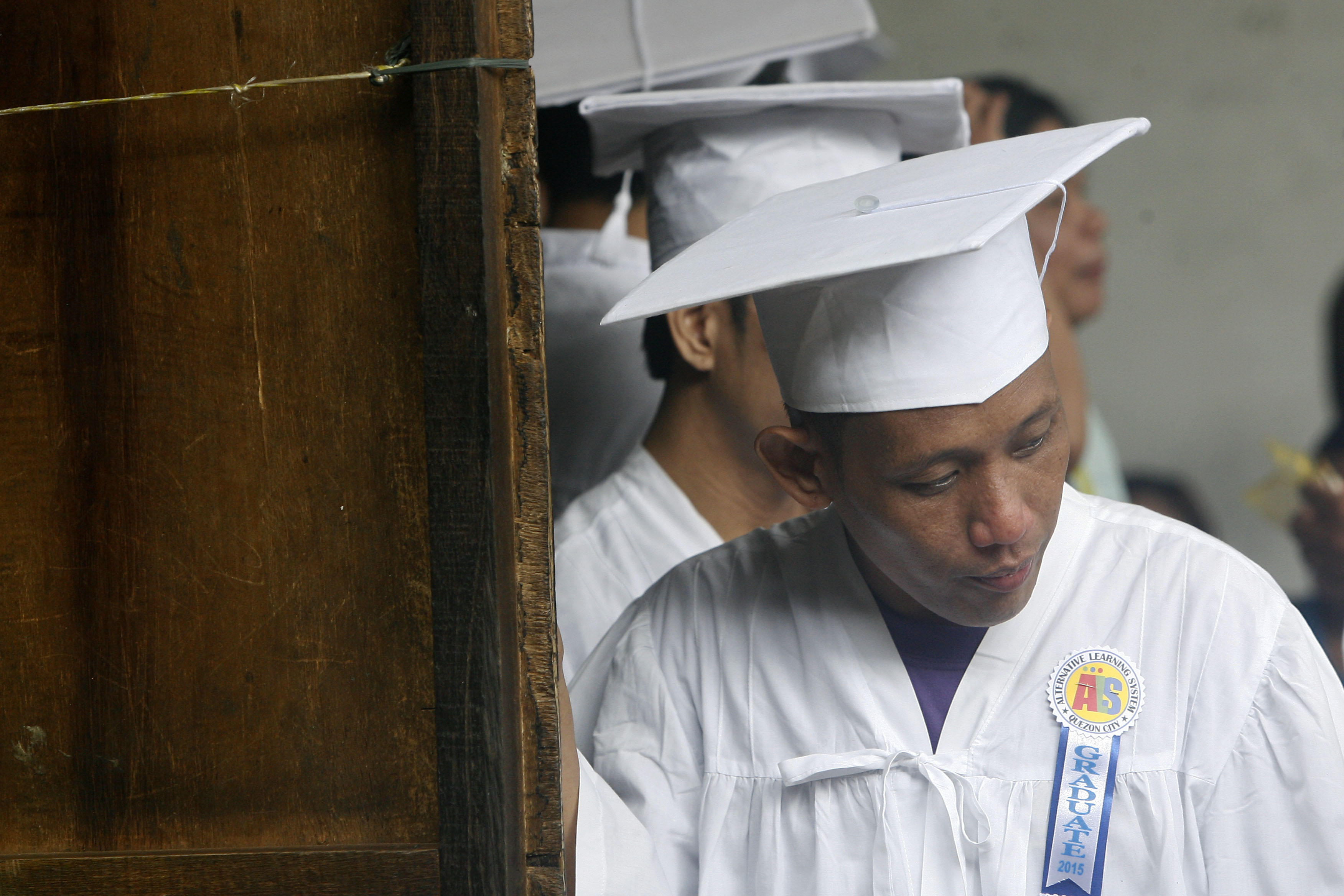 Julius Ceniza stands in front of the line, being the only elementary level graduate in the batch.