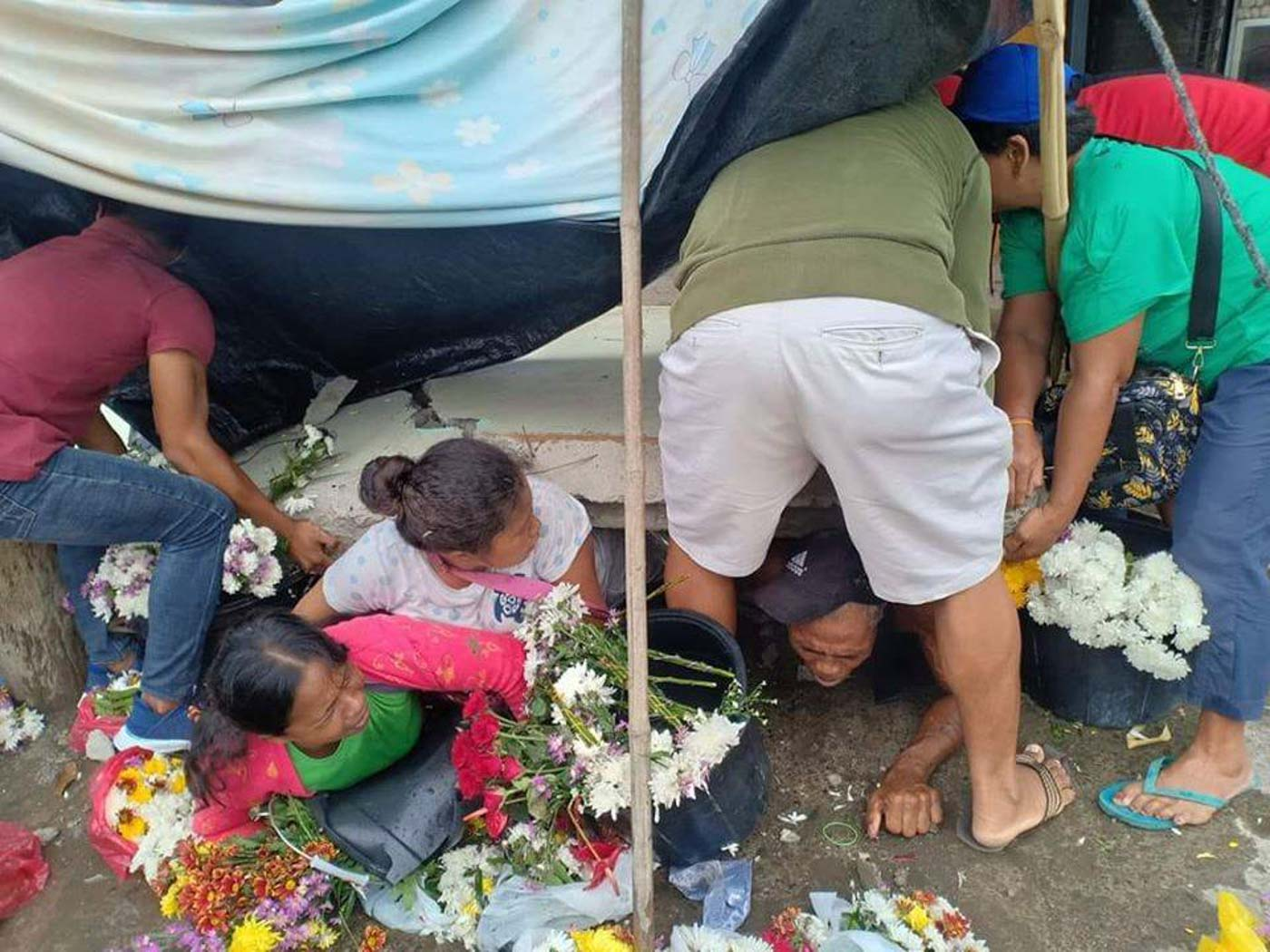 PINNED. Flower vendors at a public market in Padada, Davao del Sur, are trapped underneath a wall. Photo from John Angelo Jomao-as | via PDRRMC DavNor